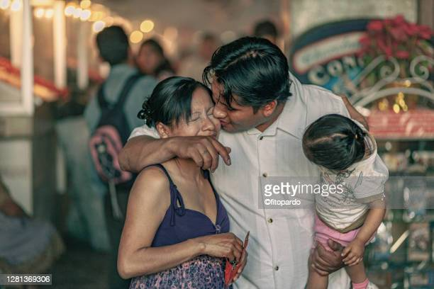 man hugs and kisses wife while carrying daughter on his arms - pocket chain stock pictures, royalty-free photos & images