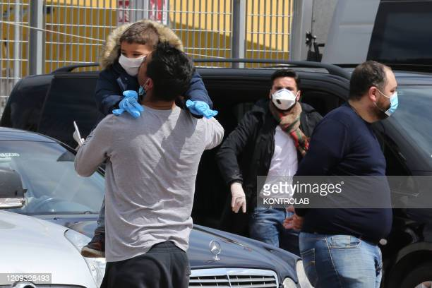 Man hugs his child just disembarked from the Catania Grimaldi ferry that brought home 105 Italian citizens who were evacuated from Tunisia. In Italy...