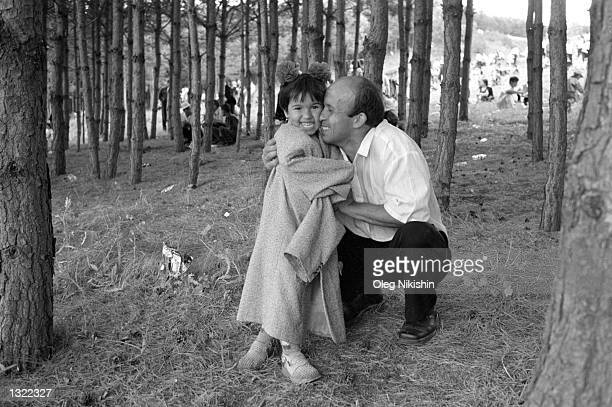 A man hugs his daughter after giving her his jacket to keep her warm June 9 2001 during the Sabantuy holiday festival in the village of Baltaci in...
