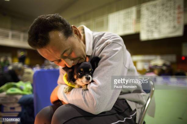 A man hugs his dog to keep it warm as earthquake victims pack an evacuation center March 20 2011 in Ofunato Iwate Japan More than a week after the...