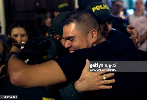 A man hugs members of the national police during a tribute to the victims of the Bogota car bomb attack in Itagui near Medellin Antioquia department...
