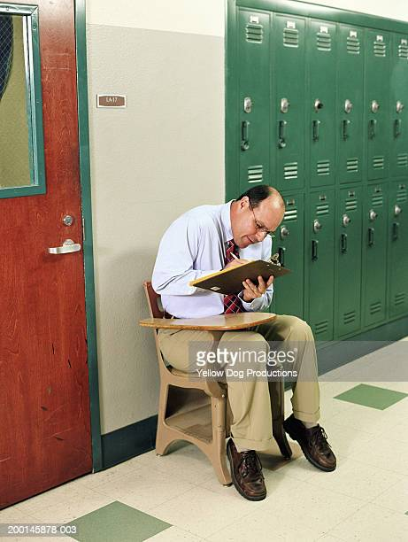 Man hunched over small desk in hallway