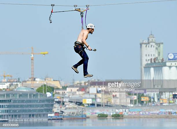 A man hung by his back skin crosses the Dniper river on a 552meter long cable between the two banks of the river on May 23 2014 in Kiev AFP PHOTO/...