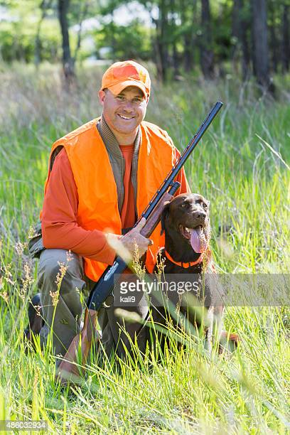 man hunting with shotgun kneeling next to retriever - hunting stock pictures, royalty-free photos & images