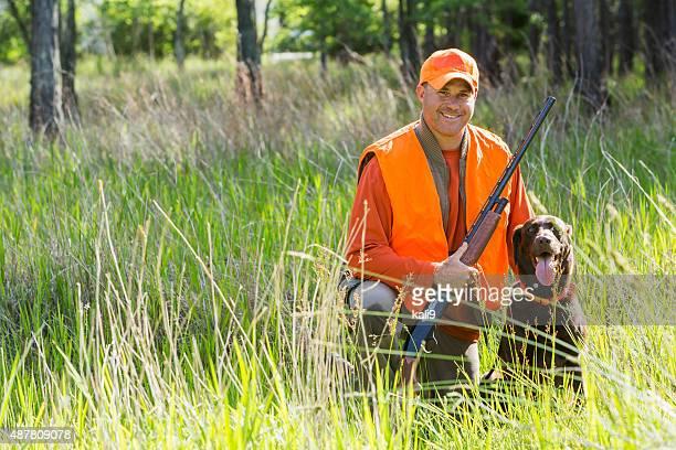 mann jagen mit der schrotflinte kniend neben retriever - jagd stock-fotos und bilder