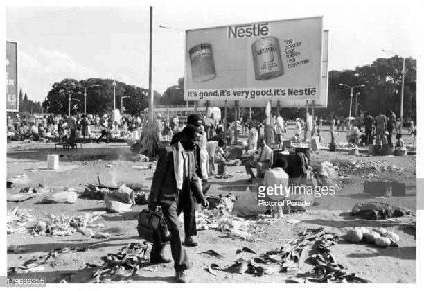 A man hurries past the market place and a Nestle billboard in SalisburyRhodesia
