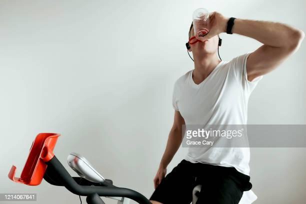 man hydrates during indoor cycling session - real body fotografías e imágenes de stock