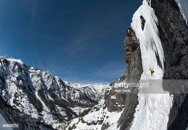 A man ice climbing a steep face with mountain views in the background near Ouray, Colorado.
