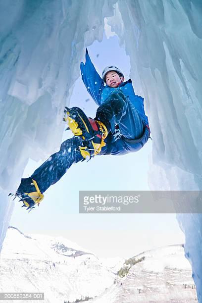 Man ice climbing, low angle view