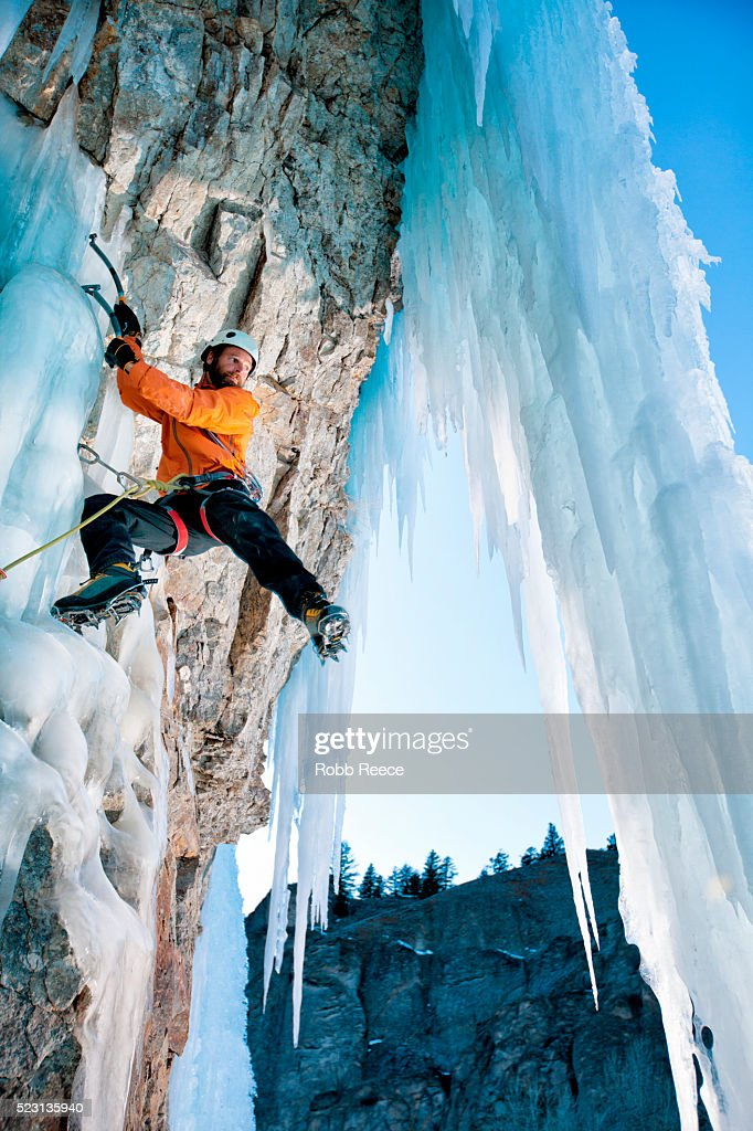 A man ice climbing on a frozen waterfall in Colorado : Stock Photo