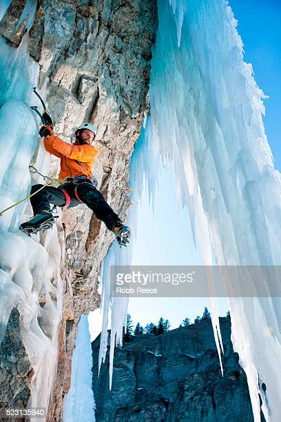 a man ice climbing on a frozen waterfall in colorado - robb reece stockfoto's en -beelden
