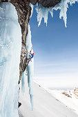Man ice climbing on frozen steep wall using ice axes