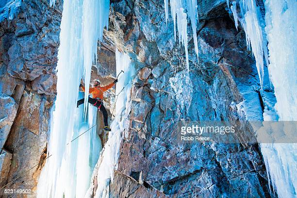 a man ice climbing on frozen waterfall in lake city, colorado - robb reece stockfoto's en -beelden