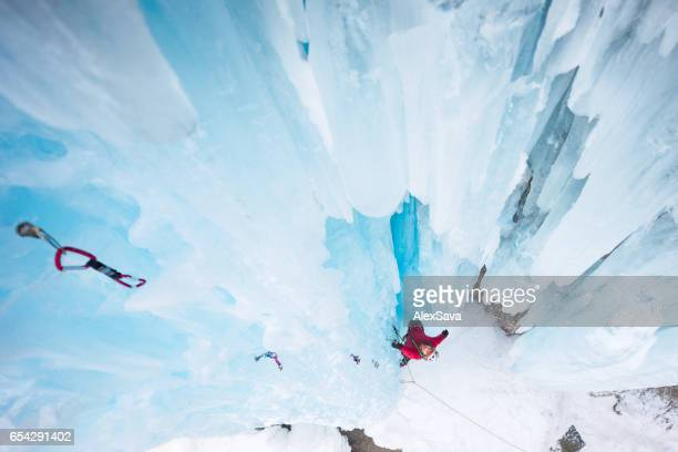 Man ice climbing on frozen waterfall in winter