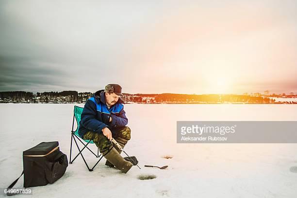 Man ice fishing in frozen lake