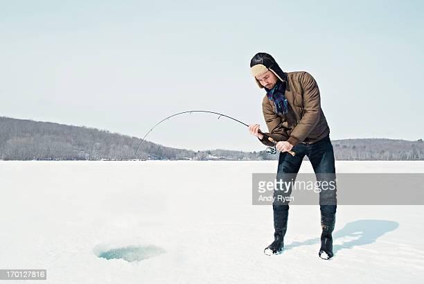 Man Ice Fishing on Frozen Lake.