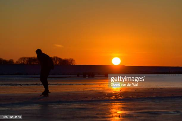 Man ice skating at sunset on the Reeve waterway in the Reevediep bypass lake near Kampen during a cold winter day in The Netherlands on February 11,...