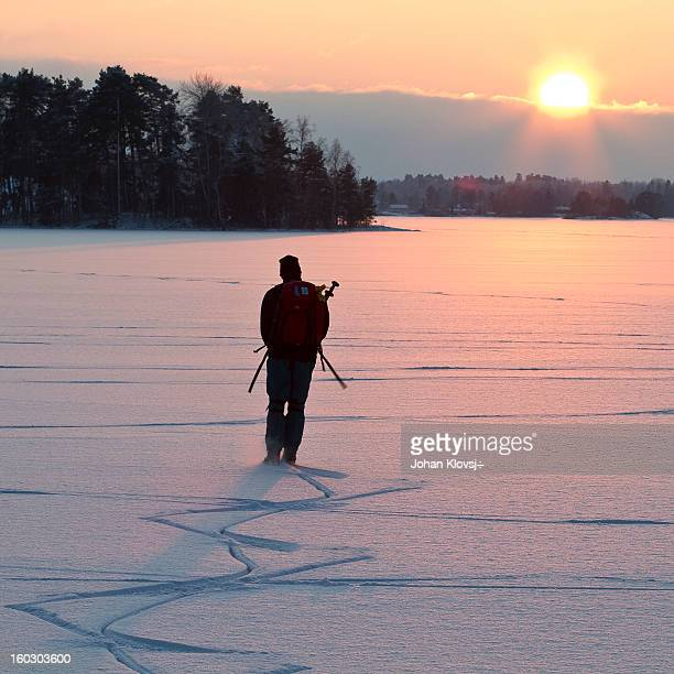 CONTENT] A man ice skating on a lake and leaving tracks in snow with the sunset in the background