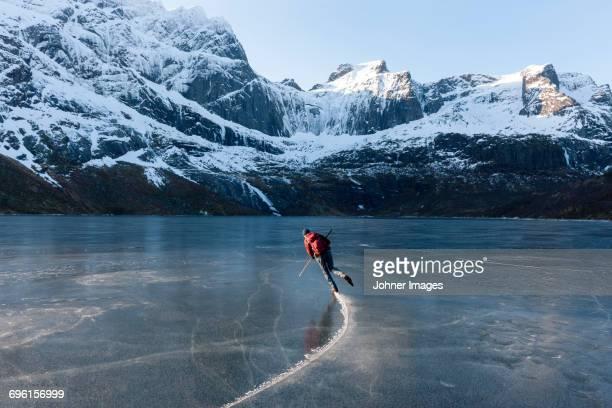 man ice-skating on frozen lake - patinar fotografías e imágenes de stock