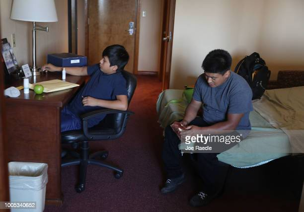A man identified only as Juan and his son Manuel relax together in their room at an Annunciation House facility after they were reunited on July 25...