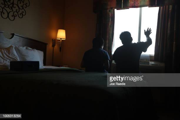 A man identified only as Juan and his son Manuel speak to each other about what they see out their window as they relax together in their room at an...