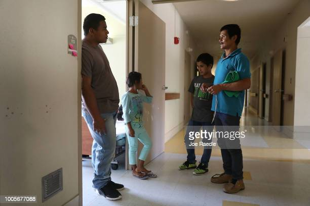 A man identified only as Luis and his daughter Selena talk with Obdulio and his son Osvin as they relax in an Annunciation House facility after they...
