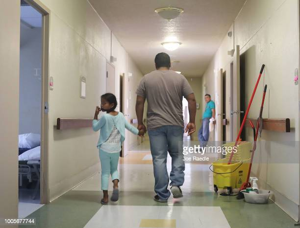 A man identified only as Luis walks through a hallway with his daughter Selena as they relax together in an Annunciation House facility after they...