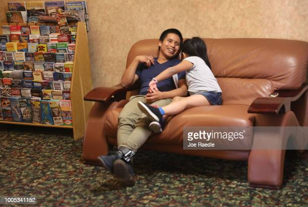A man identified only as Nery and his daughter Saylin relax as they are cared for in an Annunciation House facility after they were reunited on July...