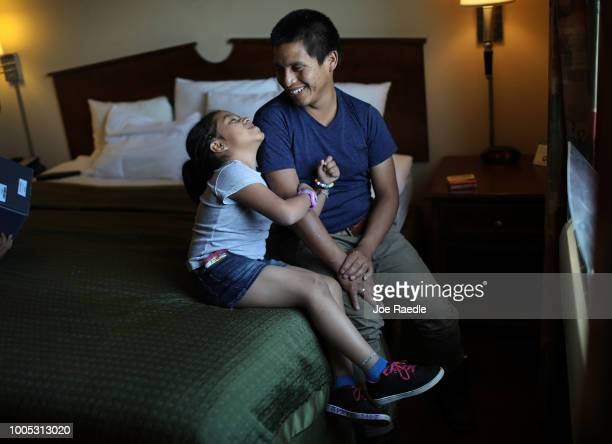A man identified only as Nery and his daughter Saylin relax together in their room as they are cared for in an Annunciation House facility after they...