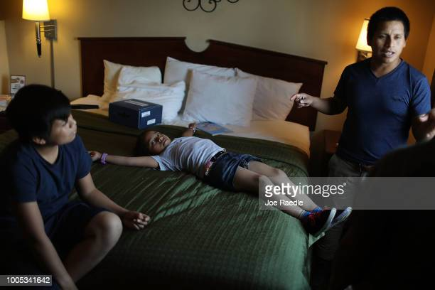 A man identified only as Nery his daughter Saylin and Manuel relax together in their shared room as they are cared for in an Annunciation House...