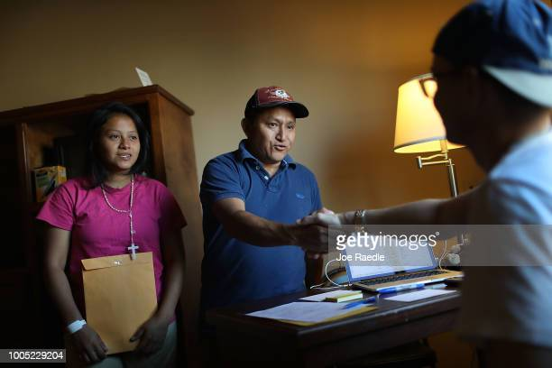 A man identified only as Santiago and his daughter Nidia thank Derek Sanchez a volunteer with the Annunciation House as he helps reunite them with...