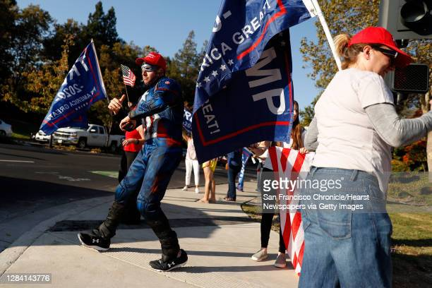 """Man identifying himself as """"Eric"""" wears a Captain America outfit as supporters of US president Donald Trump take part in a """"Trump Town USA Rally"""" at..."""