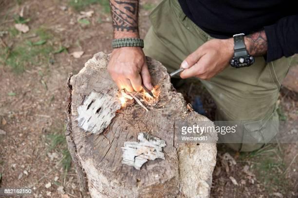 man igniting a fire on tree stump in the forest - überleben stock-fotos und bilder