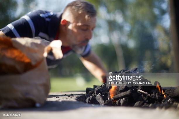 man igniting barbeque fire - igniting stock pictures, royalty-free photos & images