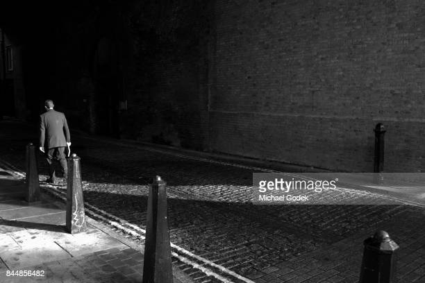 Man illuminated by a strip of light as he walks into dark alleyway