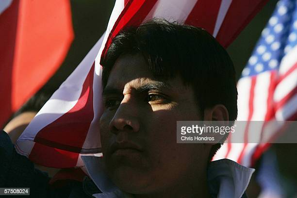 A man illuminated in afternoon light stands by various flags from the US and Latin American countries during a proimmigration rally in Union Square...