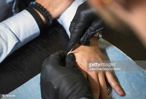 A man implants a chip with a help of a syringe during a chip implant event in Epicenter a technological hub in Stockholm on January 18 2018 An...