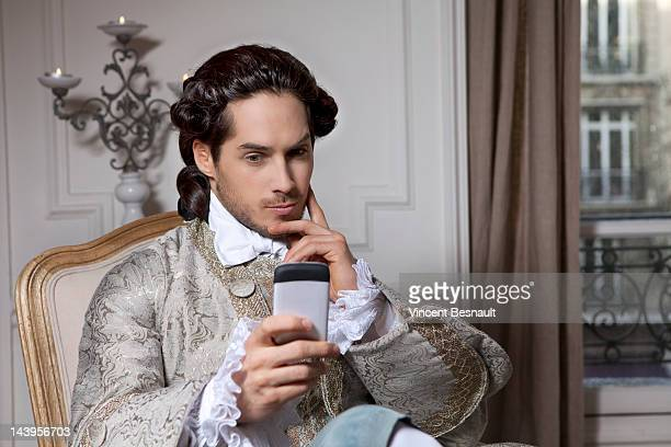 a man in 18th century costume with cell phone - 18th century stock pictures, royalty-free photos & images