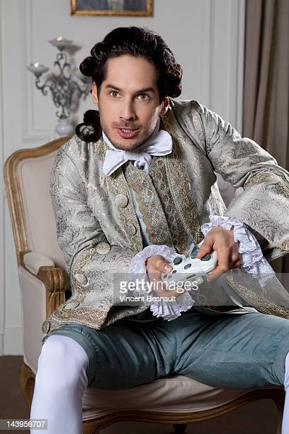 a man in 18th century garb using a games console - period costume stock pictures, royalty-free photos & images