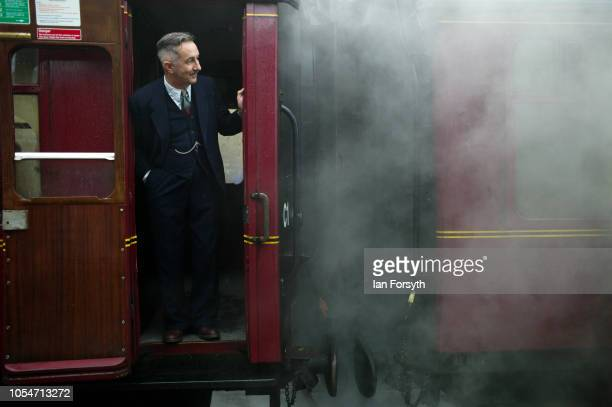 A man in 1940's period clothing stands looking from a railway carriage at Levisham station during the North Yorkshire Moors Railway 1940's Wartime...
