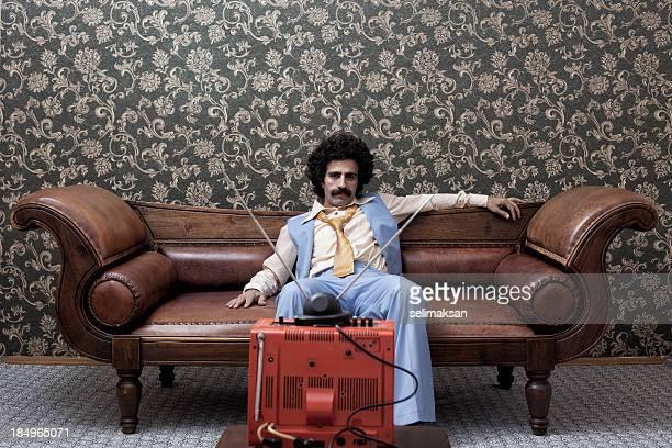 Uomo In anni'70 seduto sul divano a guardare la televisione