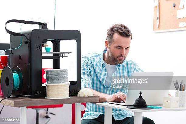 Man in 3D printer office using laptop