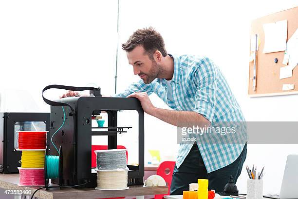 Man in 3D printer office watching printing