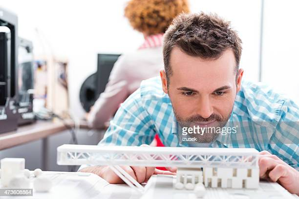 Man in 3D printer office watching printings
