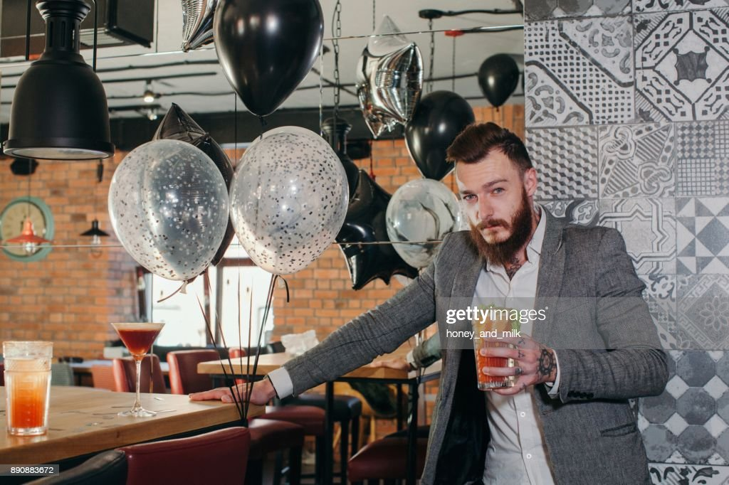 Man in a bar holding a cocktail : Stock Photo