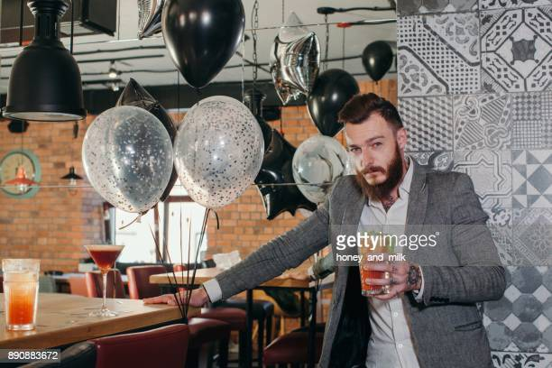 Man in a bar holding a cocktail