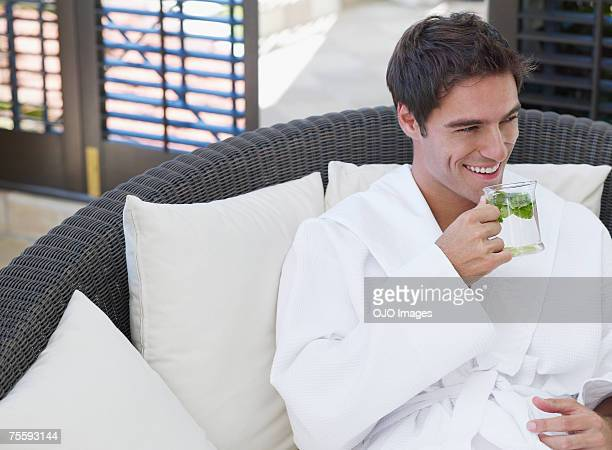 Mann in Bademantel trinken gesunde Getränke