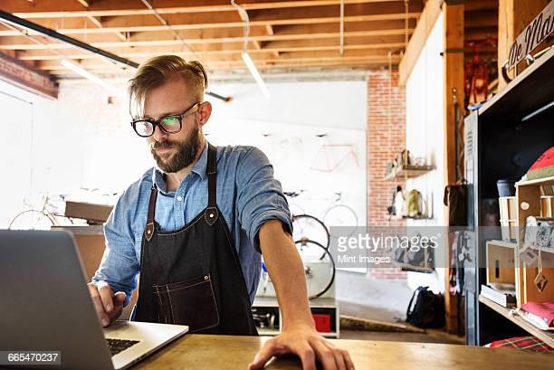 a man in a bicycle repair shop using a laptop computer. running a business. - solo un uomo di età media foto e immagini stock