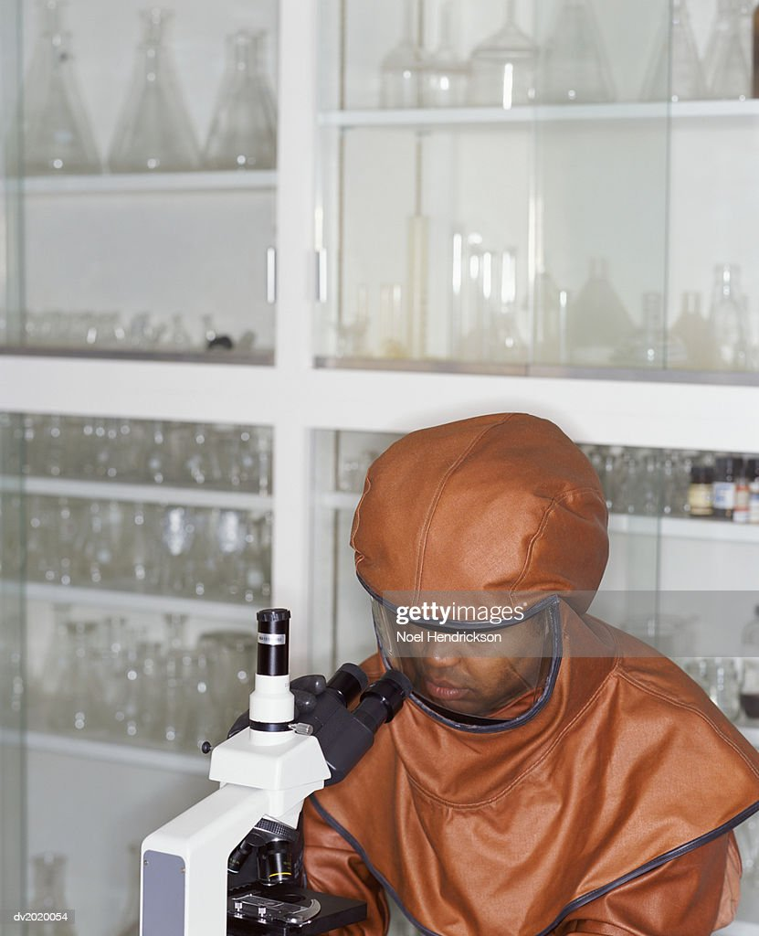 Man in a Biochemical Protection Suit Uses a Microscope in a Laboratory : Stock Photo