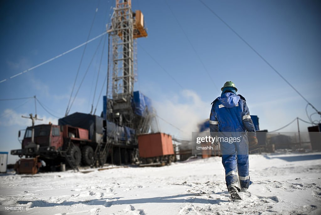 Man in a blue jumpsuit walking onto snowy construction site : Stock Photo